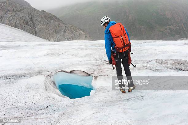 Man looks curiously at glacial moulin