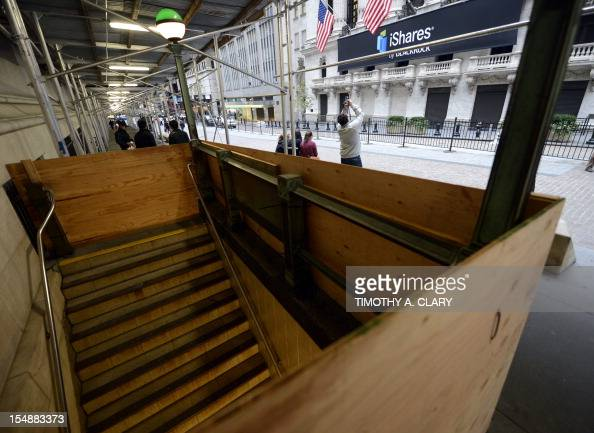 A man looks down at a boarded up Broad Street subway station across the street from the New York Stock Exchange in New York October 28 2012 as...