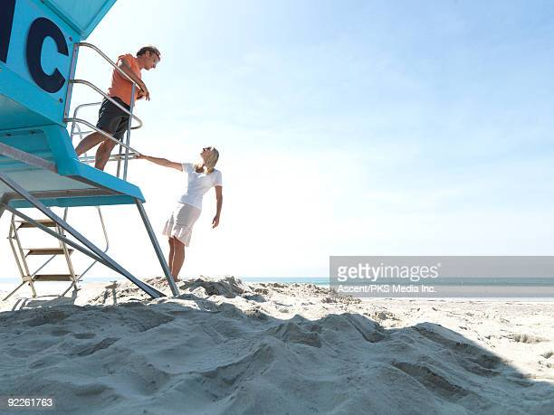 Man looks down at woman from lifeguard platform