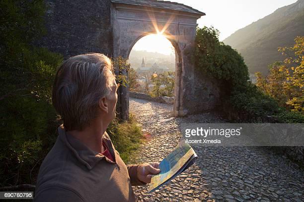 Man looks down cobblestone corridor, uses map