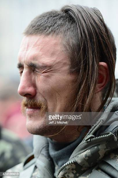 A man looks emotional as he watches the coffin of a dead antigovernment demonstrator killed in clashes with police is carried through the crowd in...