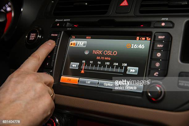 A man looks for a radio station inside a car in Oslo on January 10 2017 Norway on January 11 2017 will become the first country in the world to start...