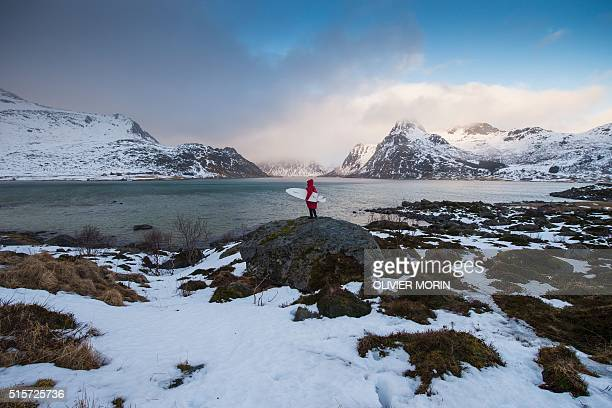 A man looks for a remote surfing spot in a fjord near Flakstad near Ramberg in Lofoten archipelago Arctic Circle on March 14 2016 / AFP / OLIVIER...