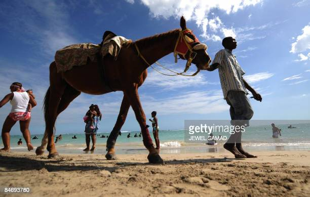 A man looks for customers to ride his horse along a beach in Kingston on February 8 2009 Jamaica has natural resources primarily bauxite and an ideal...