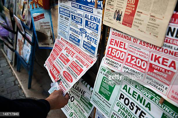 A man looks for job opportunities on newspapers in a downtown Naples shop on May 3 2012 Italy's unemployment rate hit a record of 98 percent in March...