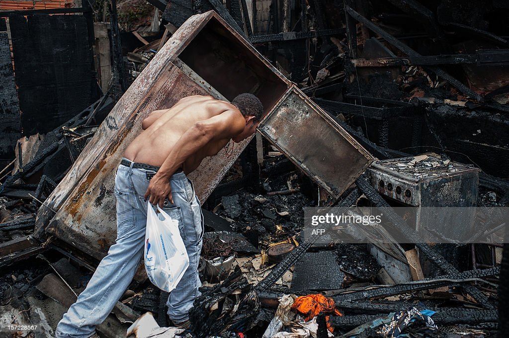 A man looks for remainings after losing his home by a fire at Paraisopolis shantytown in Sao Paulo, Brazil on November 30, 2012. According to the city's fire department, no casualty was reported and around 30 homes were burnt. AFP PHOTO/Yasuyoshi CHIBA