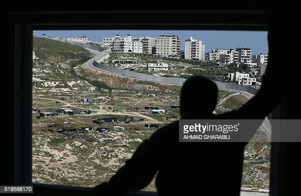 A man looks from his window at the Israeli controversial separtion barrier surrounding the east Jerusalem neighbourhood of Shuafat on April 7 2016 at...