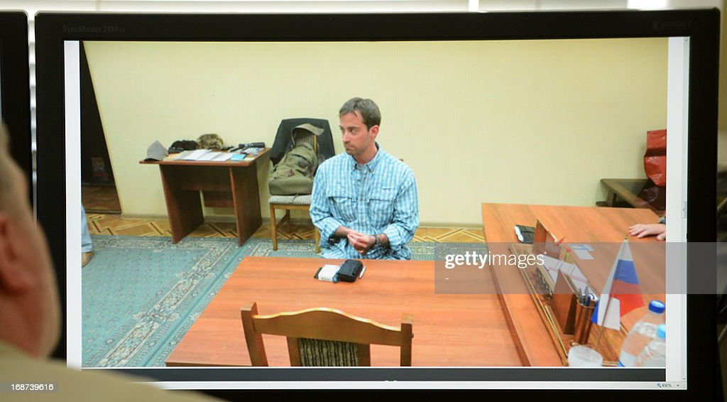 A man looks in Moscow on May 14, 2013, at a computer screen displaying a photo published by Russian state English language television RT website, which shows a man, identified as Ryan C. Fogle, the third secretary of the political section of Washington's embassy in Moscow, being questioned at the Federal Security Service after his arrest. Russia said today it had detained an alleged American CIA agent working undercover at the US embassy who was discovered with a large stash of money as he was trying to recruit a Russian intelligence officer.