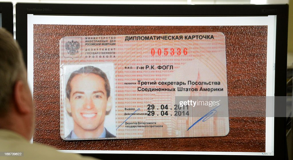 A man looks in Moscow on May 14, 2013, at a computer screen displaying a photo published by Russian state English language television RT website, which shows an ID card, of as Ryan C. Fogle, the third secretary of the political section of Washington's embassy in Moscow, being displayed at the Federal Security Service after his arrest. Russia said today it had detained an alleged American CIA agent working undercover at the US embassy who was discovered with a large stash of money as he was trying to recruit a Russian intelligence officer. AFP PHOTO / STR