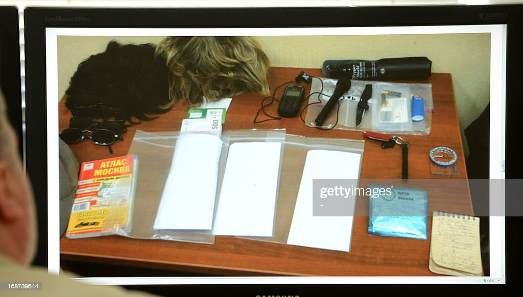 A man looks in Moscow on May 14, 2013, at a computer screen displaying a photo published by Russian state English language television RT website, which shows some of the confiscated belongings of Ryan C. Fogle, the third secretary of the political section of Washington's embassy in Moscow, being displayed at the Federal Security Service after his arrest. Russia said today it had detained an alleged American CIA agent working undercover at the US embassy who was discovered with a large stash of money as he was trying to recruit a Russian intelligence officer. AFP PHOTO / STR