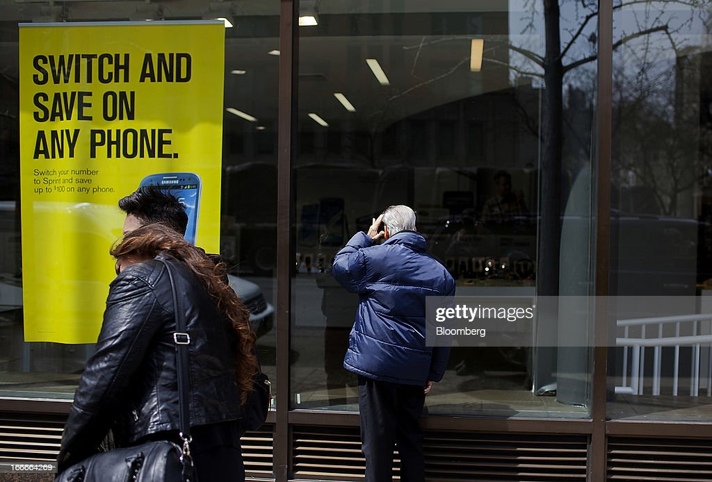 A man looks in the window of a Sprint Nextel Corp. store in New York, U.S., on Monday, April 15, 2013. Dish Network Corp., the satellite-TV company controlled by Charlie Ergen, made an unsolicited $25.5 billion offer for Sprint Nextel Corp., topping a Softbank Corp. bid for the third-largest U.S. wireless carrier. Photographer: Victor J. Blue/Bloomberg via Getty Images