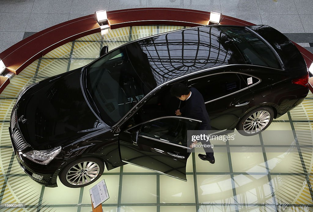 A man looks inside a Hyundai Motor Co. Equus luxury sedan in the showroom at the company's headquarters in Seoul, South Korea, on Tuesday, Jan. 22, 2013. Hyundai Motor Co. is scheduled to release fourth-quarter earnings on Jan. 24. Photographer: SeongJoon Cho/Bloomberg via Getty Images