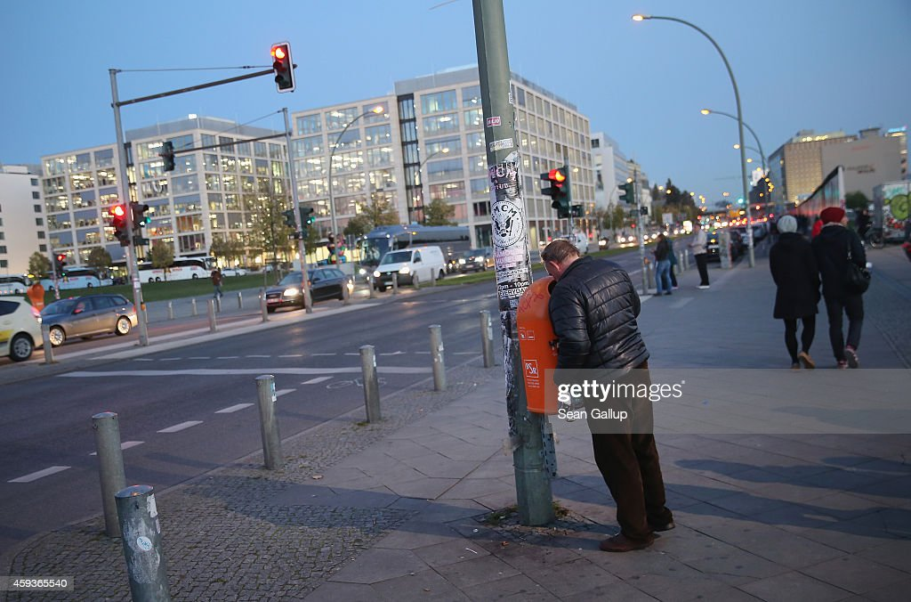 A man looks inside a trash can on October 28, 2014 in Berlin, Germany. The site of people looking in public trash cans for bottles they can cash in for the deposit is common in Berlin, which has a substantial population that lives below the official poverty level.