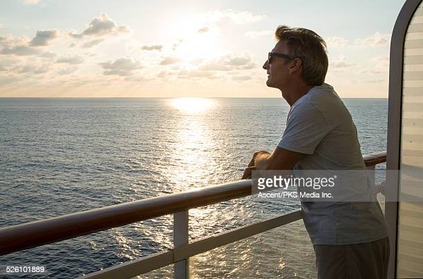 Man looks off from rail of ship at sea