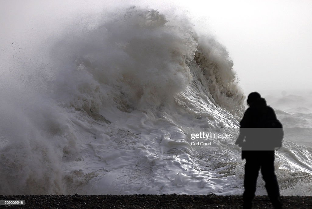 A man looks on as a wave hits the beach on February 8, 2016 in Newhaven, East Sussex. Storm Imogen is the ninth named storm to hit the UK this season. This year's storms are being named in an effort by the Met Office and Met Eireann to increase public awareness and safety. They were named by public ballot and there are no names for the letters Q, U, X, Y and Z.