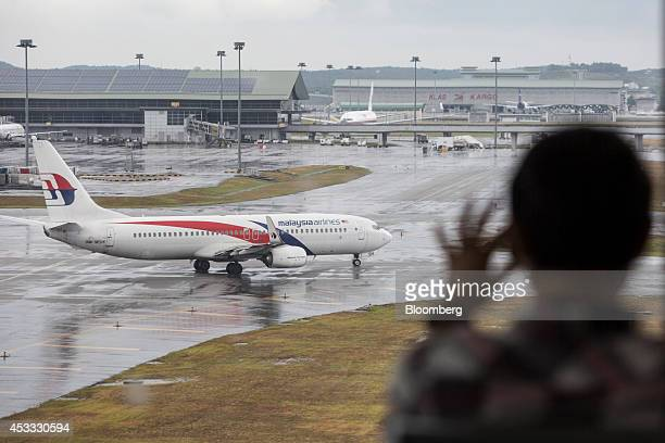 A man looks on as an aircraft operated by Malaysian Airline System Bhd taxis on the tarmac at Kuala Lumpur International Airport in Sepang Malaysia...