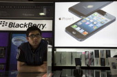 A man looks on as an Apple Inc iPhone 5 advertisement right and a Blackberry Z10 advertisement rear left are displayed in store in Connaught Place in...