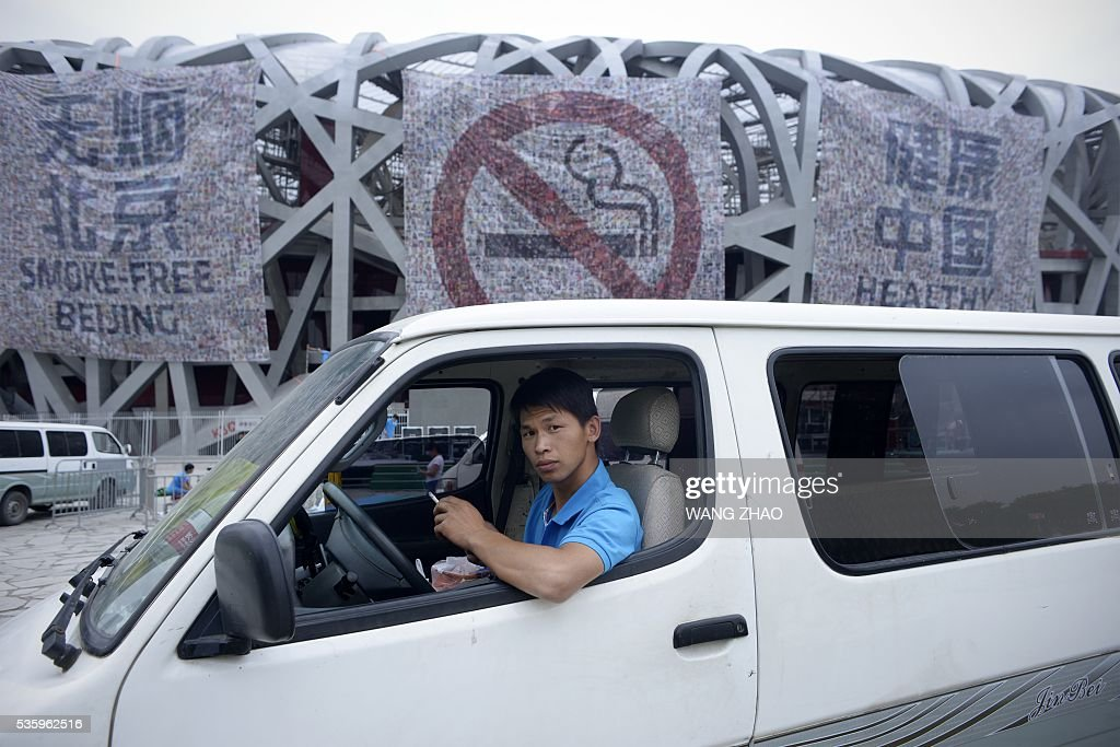 A man looks on as he smokes a cigarette in a van parked in front of a giant poster for World No Tobacco Day at the National Olympic Stadium or 'Birds Nest' in Beijing on May 31, 2016. May 31 is observed as World No Tobacco Day, with the World Health Organisation (WHO) using 'Get Ready For Plain Packaging' as the slogan of this year's day. / AFP / WANG