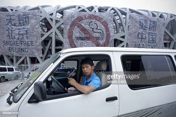 A man looks on as he smokes a cigarette in a van parked in front of a giant poster for World No Tobacco Day at the National Olympic Stadium or 'Birds...