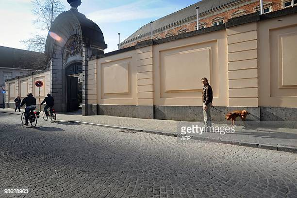 A man looks on as his dog urinates on the wall of the episcopal palace 'Het Hof van Pitthem' in the Heilige Geeststraat in Brugge on April 232010...