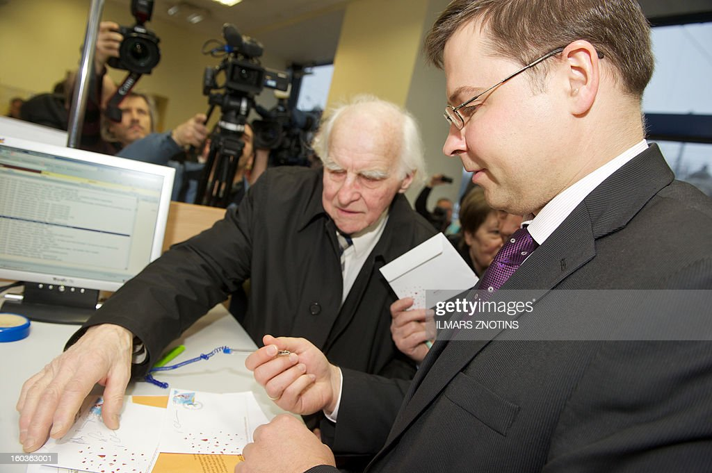 A man looks on as Latvian Prime Minister Valdis Dombrovskis (R) signs letters with the first edition of a Latvia stamp denominated in both lats and euros in Riga on January 30, 2013. Unfazed by the eurozone crisis, Latvia is poised to pass key legislation on January 31, 2013, paving the way for a request for EU approval of its entry as the zone's 18th member on January 1, 2014.