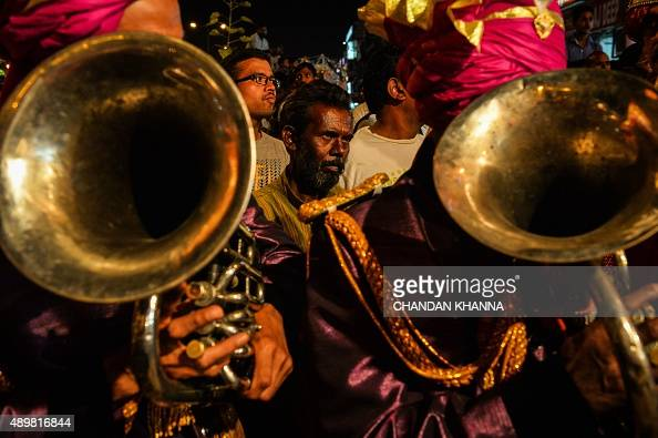 A Man Looks On As Members Of An Indian Wedding Band Play During Religious Procession For The Hindu Festival Ganesh Chaturthi In New Delhi September 24