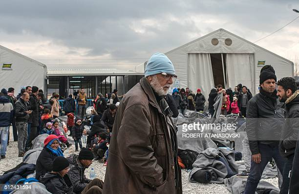 A man looks on as migrants and refugees rest in a camp as they wait for a train to Serbia near Gevgelija on the MacedonianGreek border on February 26...
