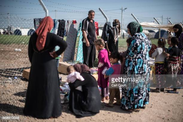 A man looks on as women browse clothes for sale on his market stall in Khazir refugee camp on April 15 2017 near Mosul Iraq Khazir camp with a...