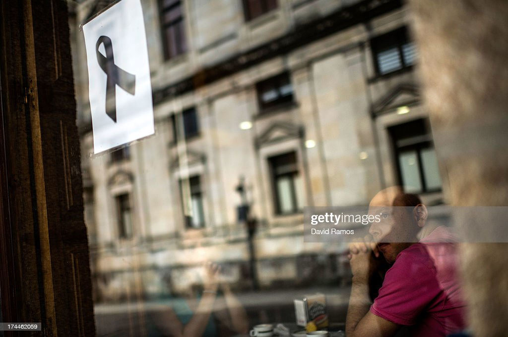 A man looks on from a cafe as a poster with a black ribbon on is displayed on the window in memory of the victims of the train crash , on July 26, 2013 in Santiago de Compostela, Spain. The high speed train crashed after it derailed on a bend as it approached the north-western Spanish city of Santiago de Compostela at 8.40pm on July 24th. At least 78 people have died and a further 131 are reported injured. The crash occured on the eve of the Santiago de Compostela Festivities.