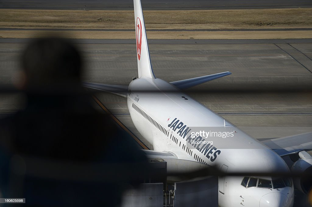 A man looks on from an observation deck as a Boeing Co. 767 aircraft operated by Japan Airlines Co. (JAL) stands parked at Haneda Airport in Tokyo, Japan, on Sunday, Feb. 3, 2013. Japan Airlines, the nation's largest carrier by market value, is scheduled to release earnings on Feb. 4. Photographer: Akio Kon/Bloomberg via Getty Images