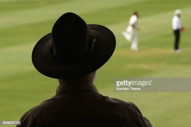 A man looks on from the grandstand as Chadd Sayers of the Redbacks bowls during the Sheffield Shield final between Victoria and South Australia on...