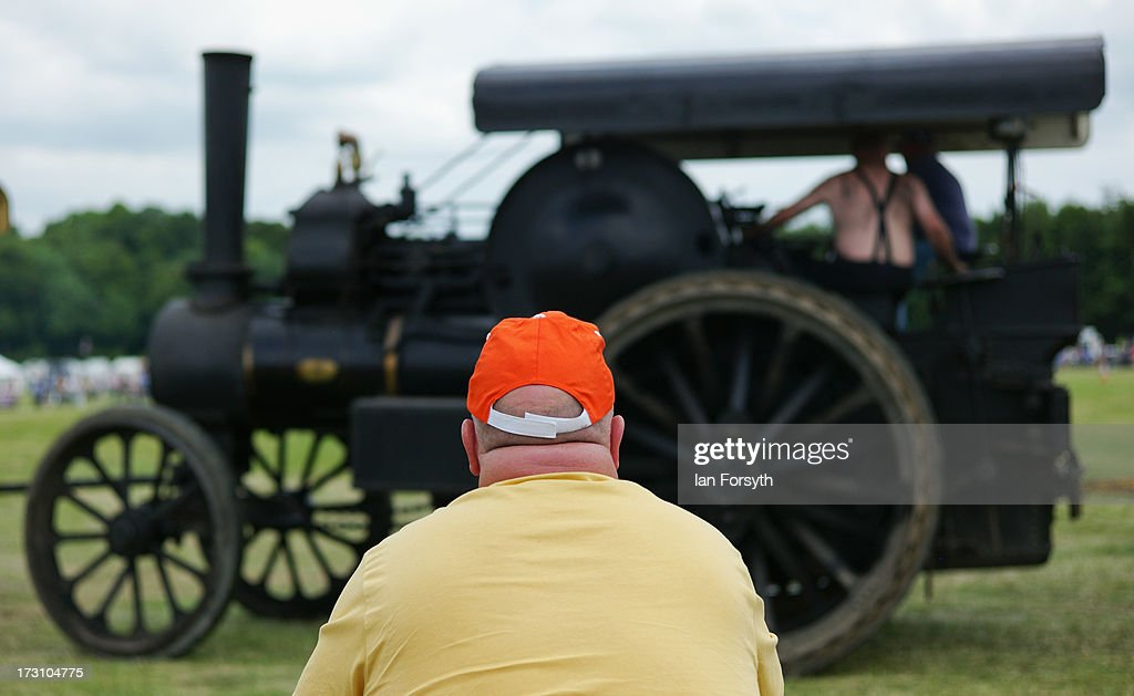 A man looks on from the side of the main arena at the steam rally at Duncombe Park on July 7, 2013 in Helmsley, England. The popular steam rally takes place in the magnificant grounds of the park over the first weekend of July each year and brings together traction engines, working displays, vintage tractors, commercial and military vehicles, vintage cars and motorcycles.