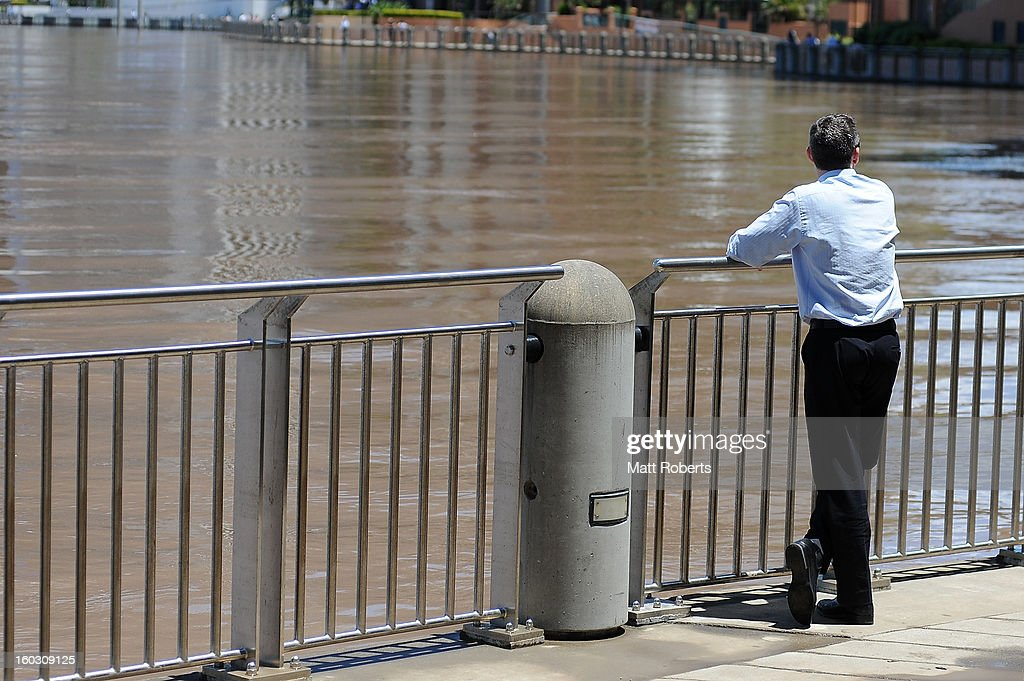 A man looks on in the CBD as the Brisbane river passes it high tide peak as parts of southern Queensland experiences record flooding in the wake of Tropical Cyclone Oswald on January 29, 2013 in Brisbane, Australia. The river in the Brisbane CBD is expected to peak at 2.3 metres today - lower than the 2.6 metre peak predicted - but is still likely to flood low-lying properties and businesses. The flood crisis has claimed four lives so far, with the city of Bundaberg, Queensland faces the worst flooding in its history.