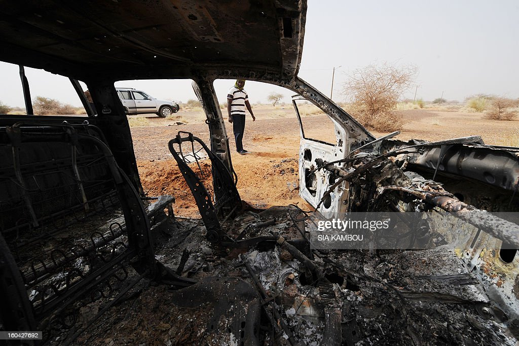 A man looks on January 31, 2013 at a vehicle, belonging to Islamists of the Movement for Oneness and Jihad in West Africa (MUJAO), that was destroyed by French air strikes in the northern Malian city of Gao. The city that was controlled by Islamists, who applied Islamic sharia law, was retaken on January 26 by French and Malian troops in a major boost to the French-led offensive against the Al Qaeda-linked rebels, who have been holding Mali's vast desert north since last April.