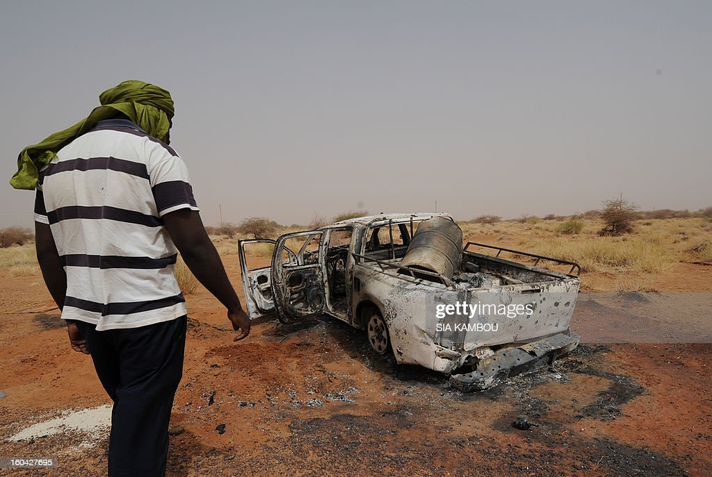 A man looks on January 31, 2013 at a vehicle, belonging to Islamists of the Movement for Oneness and Jihad in West Africa (MUJAO), that was destroyed by French air strikes in the northern Malian city of Gao. The city that was controlled by Islamists, who applied Islamic sharia law, was retaken on January 26 by French and Malian troops in a major boost to the French-led offensive against the Al Qaeda-linked rebels, who have been holding Mali's vast desert north since last April. AFP PHOTO / SIA KAMBOU