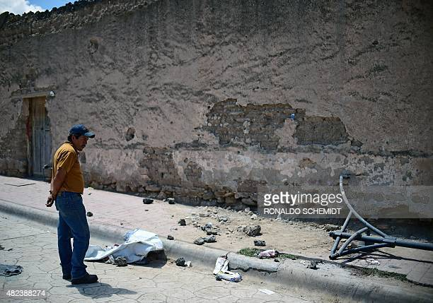 A man looks on July 30 2015 at the site where a truck plowed into a crowd of pilgrims in Mazapil Zacatecas State northcentral Mexico The truck plowed...