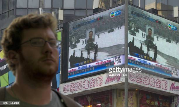 A man looks on near an electronic display in Hong Kong showing a portrait of North Korea's late leader Kim Jongil placed on top of a car at his...