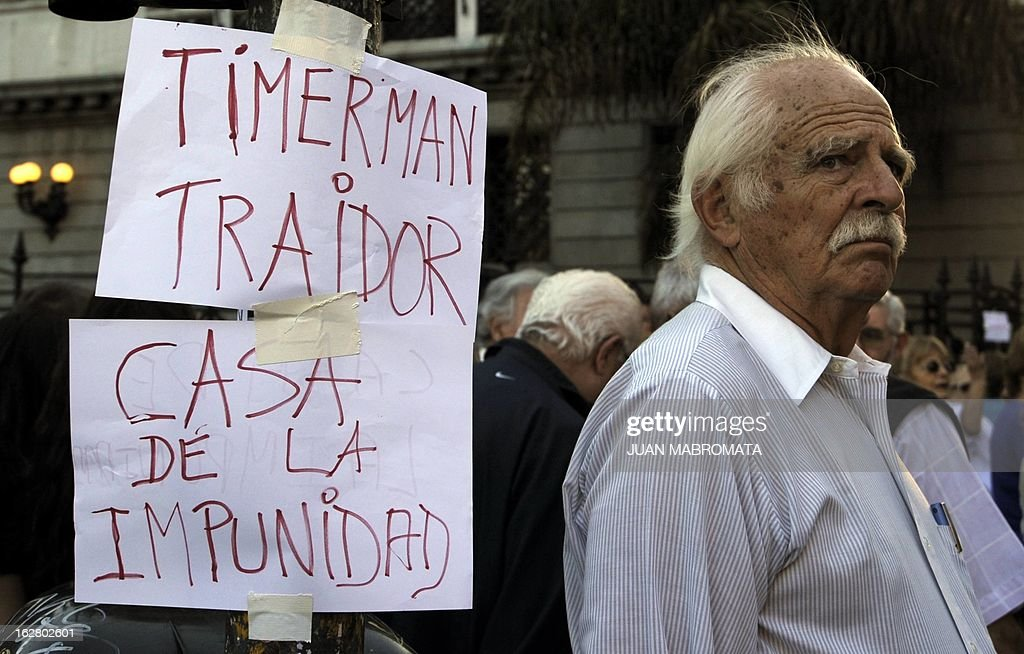 A man looks on next to signs reading 'Timmerman traitor' and 'House of impunity' outside the Congress building in Buenos Aires on February 27, 2013, while legislatives discuss the possibility of an agreement with Iran to establish a truth commission over a terrorist attack that took place in 1994. Eight Iranian nationals are still wanted in connection with the bombing of the Argentine Israelite Mutual Association (AMIA is Spanish), which left 85 dead and 300 wounded. AFP PHOTO / Juan Mabromata