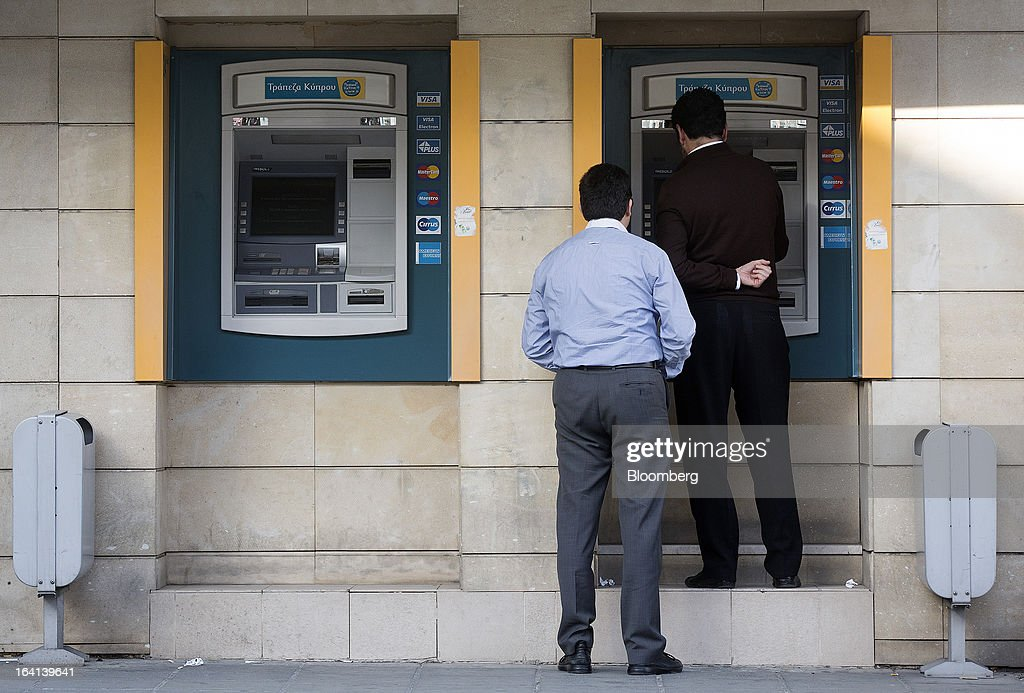 A man looks on while a customer uses an automated teller machine (ATM) to withdraw cash outside a Bank of Cyprus Plc branch in Nicosia, Cyprus, on Wednesday, March 20, 2013. European policy makers weighed how far to push Cyprus after lawmakers in the Mediterranean nation rejected an unprecedented levy on bank deposits, throwing into limbo a rescue package designed to keep it in the euro. Photographer: Simon Dawson/Bloomberg via Getty Images