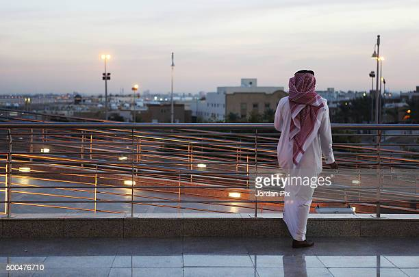 A man looks on while others arrive to participate at the first annual Bab Rizq Jameel a job opportunity fair for Saudi youth that is taking place at...