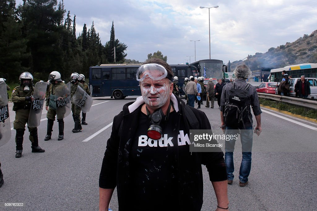 A man looks on with a gas mask as clashes break out on the highway after police blocked the road from a planned pension reform protest outside the Agriculture ministry on February 12, 2016 in Athens, Greece. Around reportedly 800 protesters from Crete gathered outnumbering police who were armed with teargas.