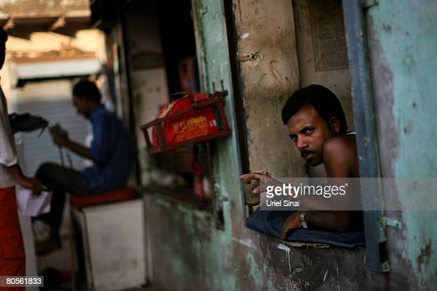 A man looks out a window at the Dharavi slum said to be 'Asia's largest slum' April 2008 in Mumbai India A city redevelopment program to convert this...