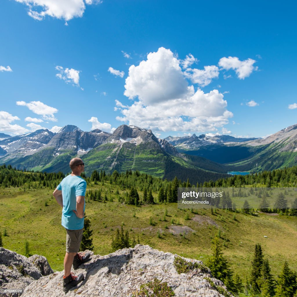 Man looks out across mountain landscape