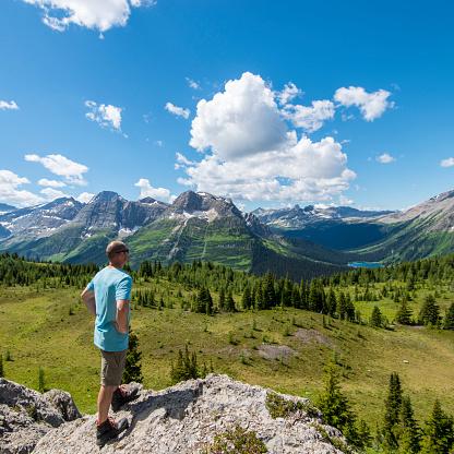 Man looks out across mountain landscape