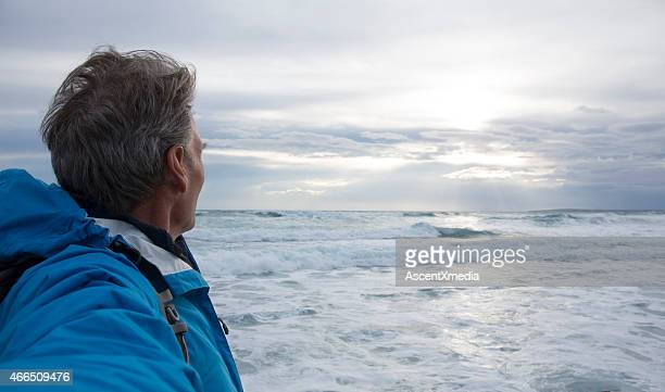 Man looks out across sea after storm