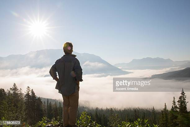 Man looks out across valley fog and mountains