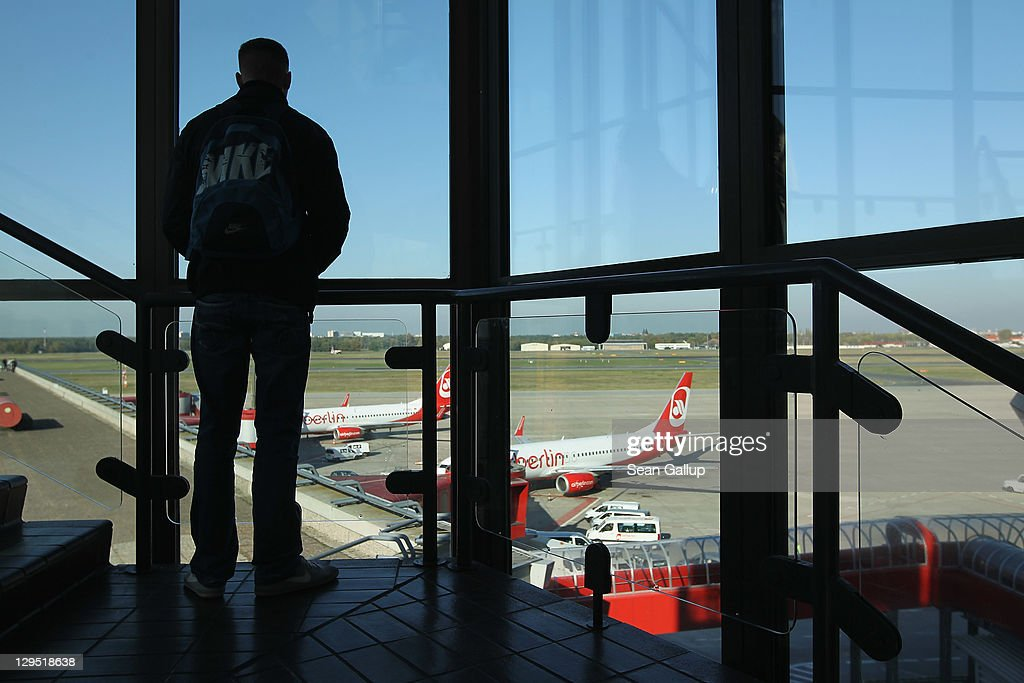 A man looks out at Air Berlin passenger planes from the main terminal at Tegel Airport on October 17 2011 in Berlin Germany Tegel which first went...