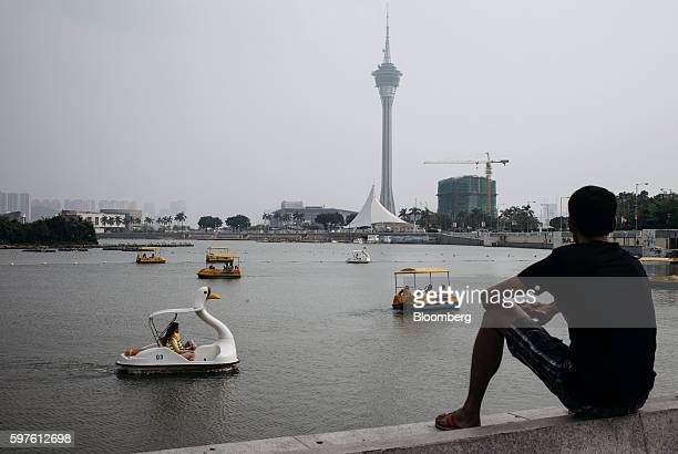 A man looks out at people riding on pedal boats at the Nam Van Lake as Macau Tower center stands in the background in Macau China on Sunday Aug 28...
