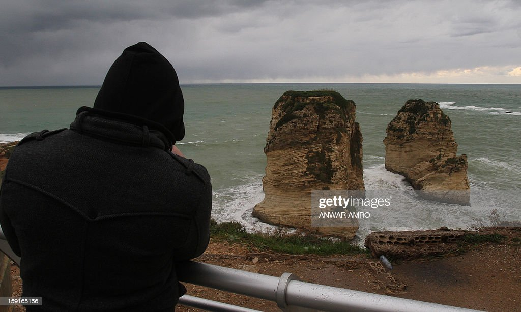 A man looks out at the famous Pigeon Rocks from the promenade in Beirut in stormy weather conditions on January 9, 2013. A met office official at Beirut airport said the storm would continue and that lower temperatures would result in snowfall in the mountains as low as 300 metres (1,000 feet).