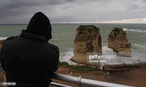 A man looks out at the famous Pigeon Rocks from the promenade in Beirut in stormy weather conditions on January 9 2013 A met office official at...